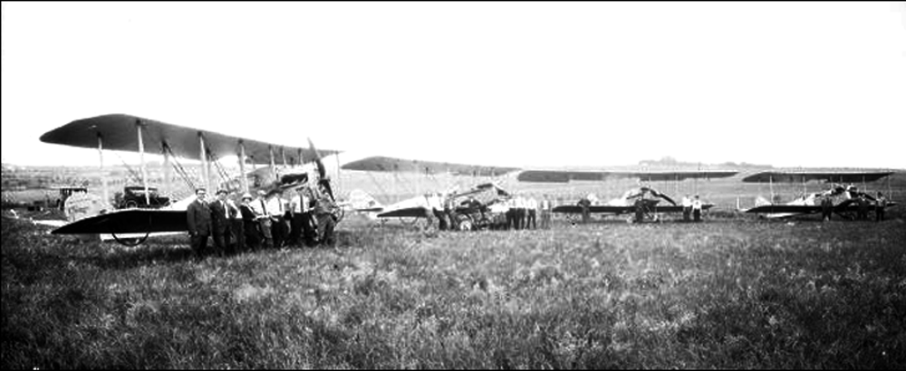 Four Lincoln Standard airplanes parked on a grassy field. Surrounding each plane is a pilot and crew. - Image courtesy of Nebraska History, http://nebraskahistory.pastperfectonline.com